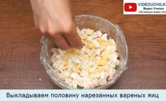 Выкладываем половину нарезанных вареных яиц