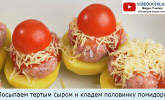 Посыпаем тертым сыром и кладем половинку помидора